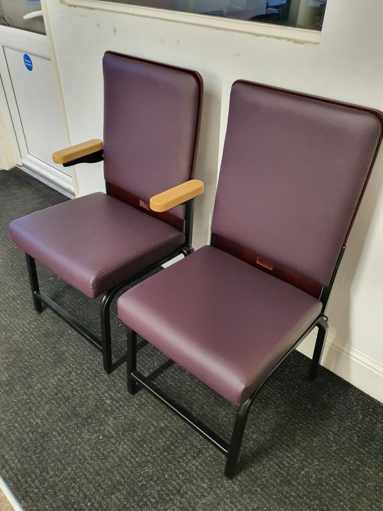 two stackable auditorium chairs with purple leather upholstery. One has flipping wooden arms.